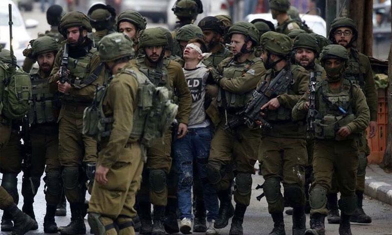 طفل فلسطيني بين مجموعة من الجنود الإسرائيلين في مدينة الخليل الفلسطينية (EFE)