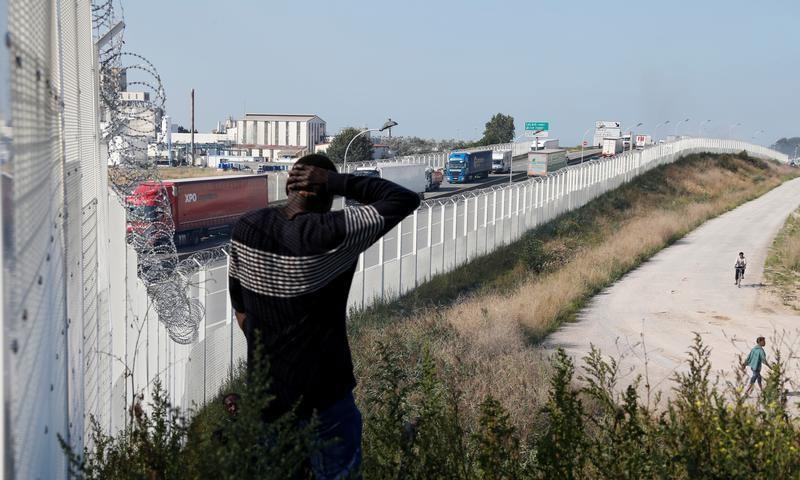 """مخيم """"كاليه"""" في فرنسا، ولاجئين بالقرب من السياج الفاصل عن بريطانيا (رويترز)"""