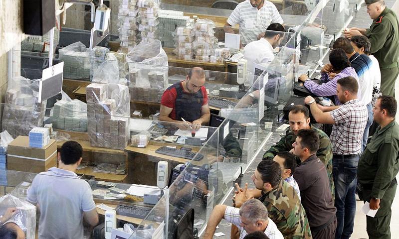 موظفون وعسكريون ينتظرون رواتبهم في البنك المركزي السوري - 30 حزيران 2015 (AFP)