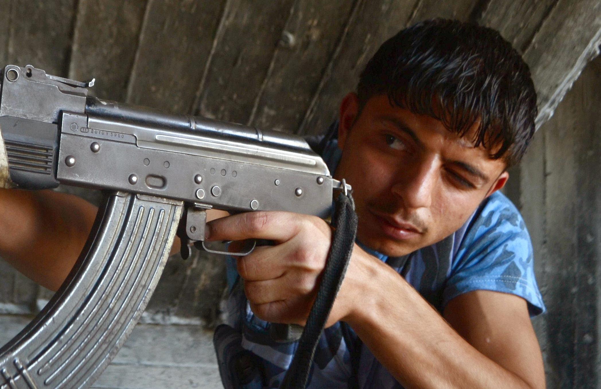 شاب سوري من المعارضة السورية يوجه سلاحه في مدينة حلب (AFP)
