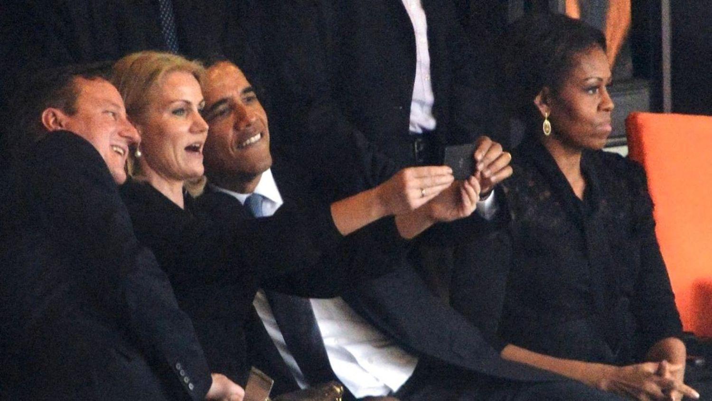 الرئيس الأمريكي السابق باراك أوباما يلتقط صورة سيلفي مع رئيسة وزراء الدنمارك (AFP)