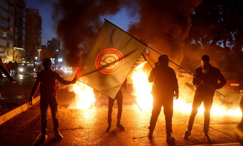 مؤيدو حركة أمل يحملون علم الحزب بالقرب من الإطارات المحترقة في بيروت 29 كانون الثاني 2018 (رويترز)