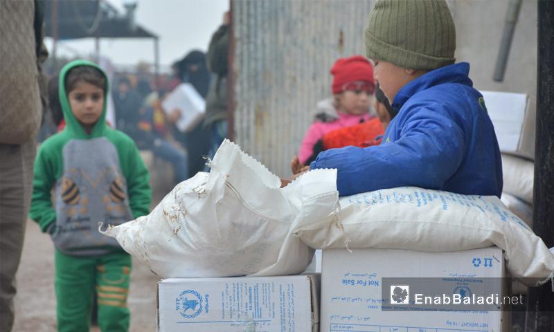"""أطفال يقفون قرب سلل """"برنامج الأغذية العالمي"""" في ريف إدلب - كانون الثاني 2018 (عنب بلدي)"""