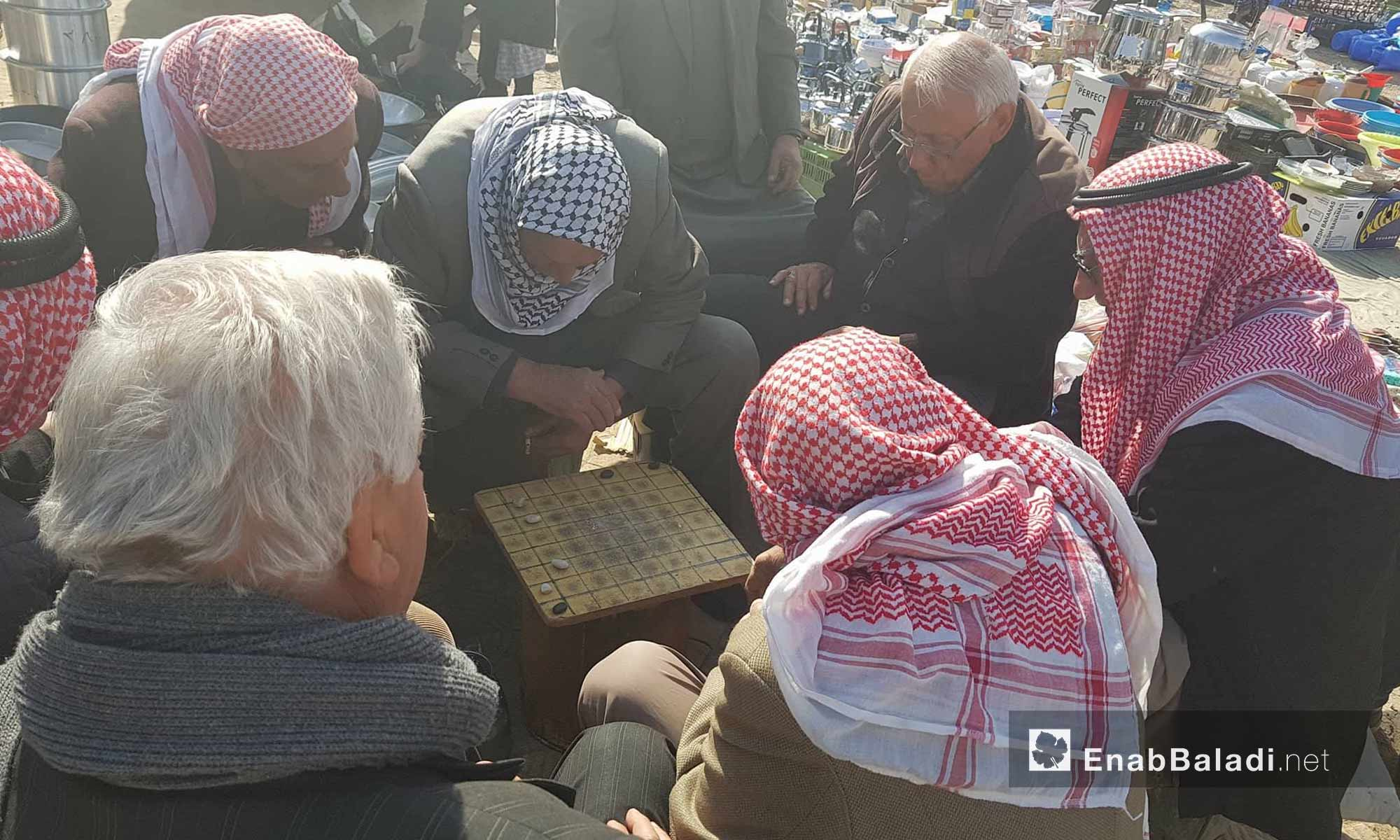 مسنون يلعبون لعبة محلية في سوق حطين في مدينة القامشلي - 4 شباط 2018 (عنب بلدي)