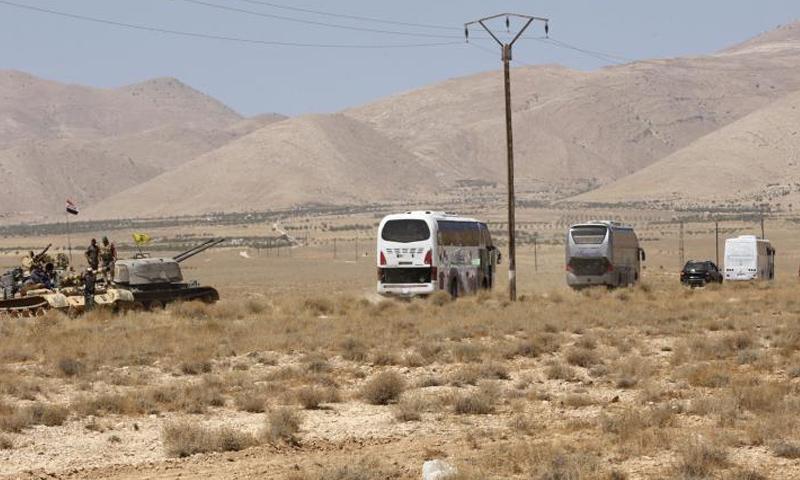 عناصر من قوات الأسد وحزب الله بجوار حافلات لتنظيم الدولة أثناء إخراجهم من القلمون - (انترنت)