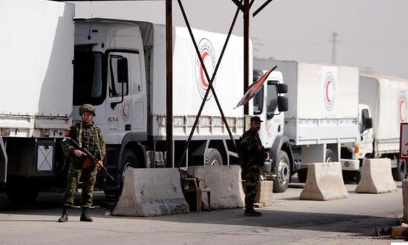 جنود روس يقومون بتأمين قافلة مساعدات بالقرب من العاصمة السورية دمشق - 5 آذار 2018 (رويترز)