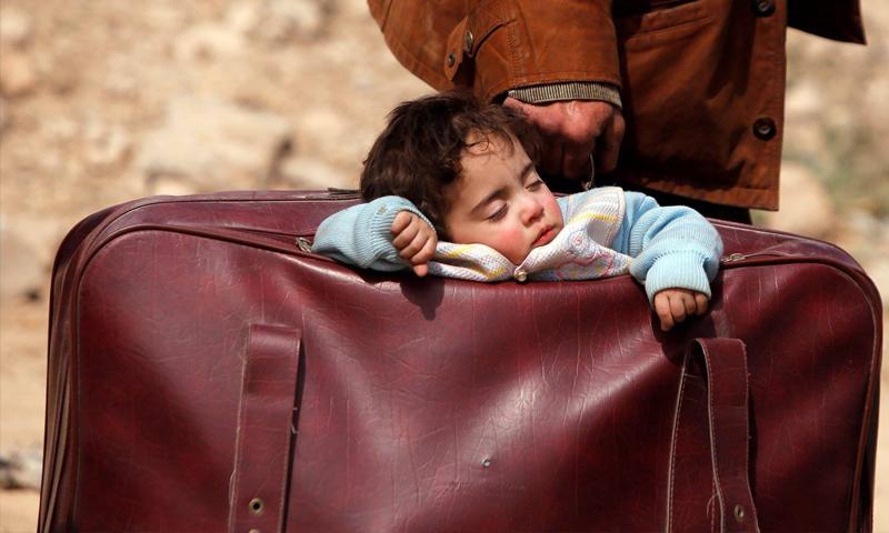 طفل نائم في حقيبة والده أثناء مغادرة الغوطة باتجاه مناطق سيطرة قوات الأسد - 14 آذار 2018 (رويترز)