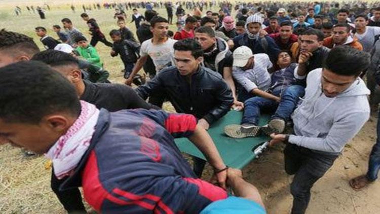 فلسطينيون يحملون شابا على محفة أصيب خلال اشتباكات مع القوات الاسرائيلية على الحدود مع غزة في 30 آذار 2018(رويترز)