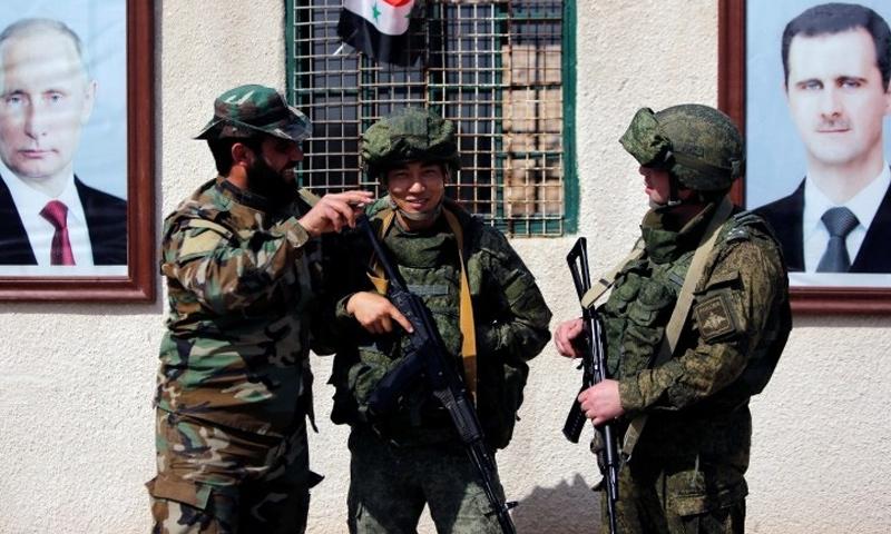 جندي من قوات الأسد مع جنود روس على معبر مخيم الوافدين في الغوطة الشرقية - شباط 2018 (رويترز)