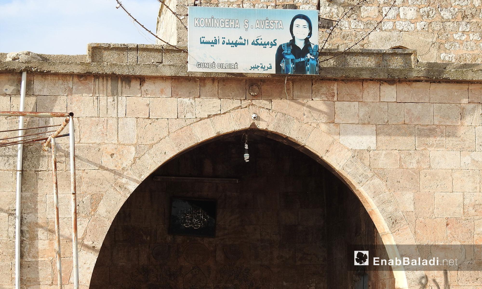 """لافتة لإحدى مقاتلات """"الوحدات"""" الكردية خلال جولة على الطريق بين قرى جلبل ومريمين وأناب في عفرين - 11 آذار 2018 (عنب بلدي)"""