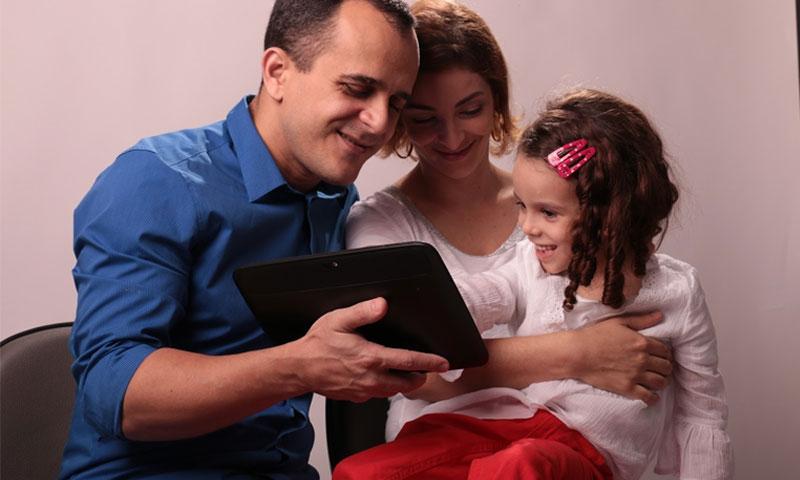 """كلارا مع والديها أثناء استخدام تطبيق """"ليفوس"""" (Livox)"""