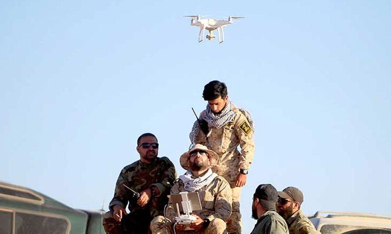 عناصر من حركة النجباء العراقية يسيرون طائرة درونز على الحدود السورية العراقية (وكالة مهر الإيرانية)