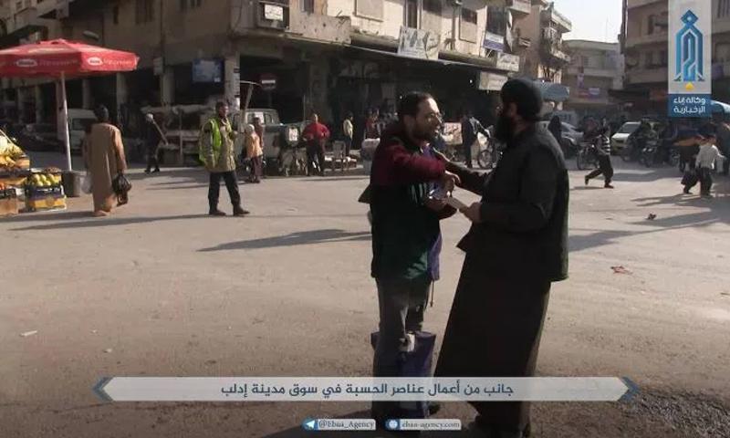 """عنصر من """"سواعد الخير"""" وسط مدينة إدلب - 2018 (وكالة إباء)"""