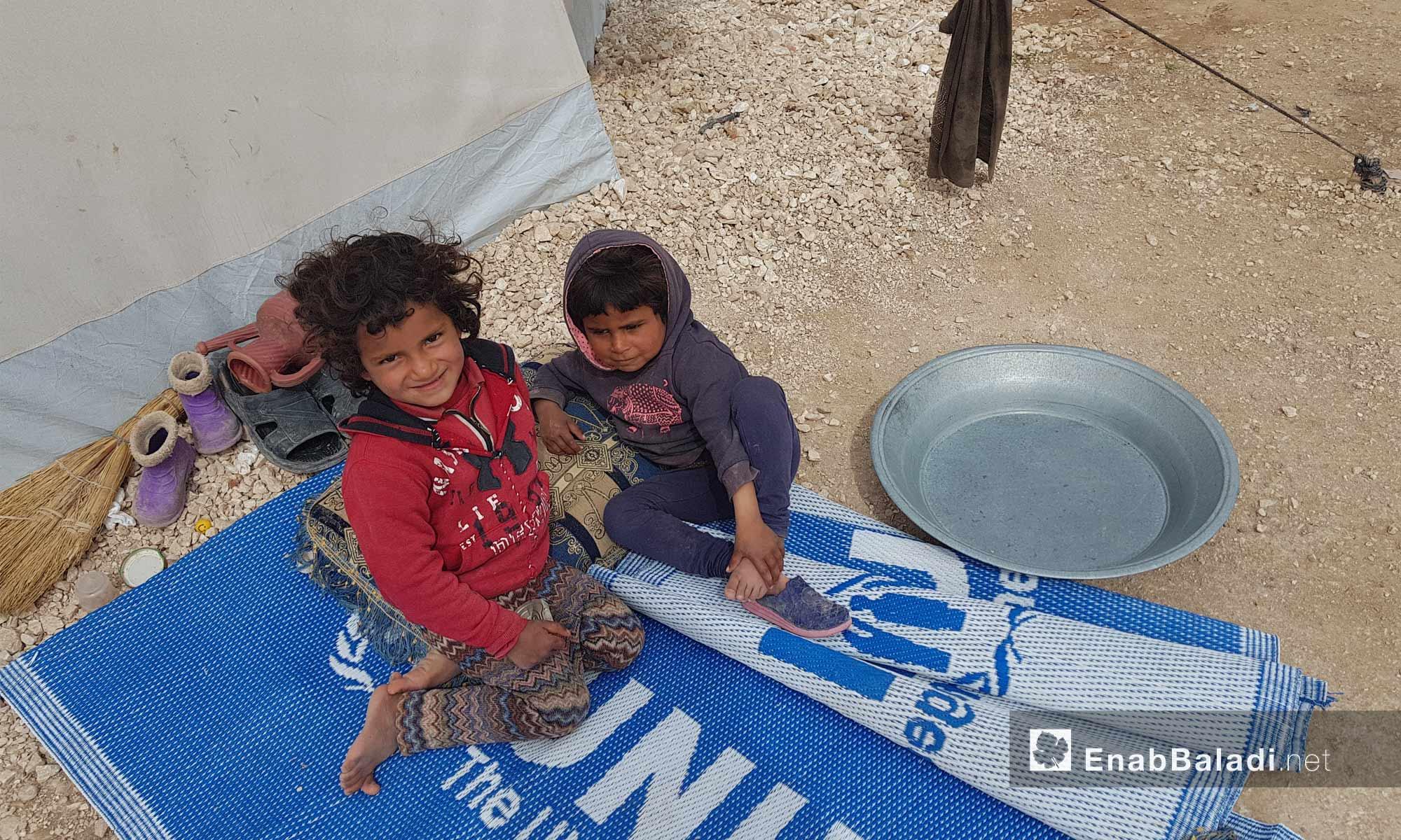 طفلتان تجلسان بالقرب من خيمة في مخيم العريشة بريف الحسكة الجنوبي - 9 آذار 2018 (عنب بلدي)