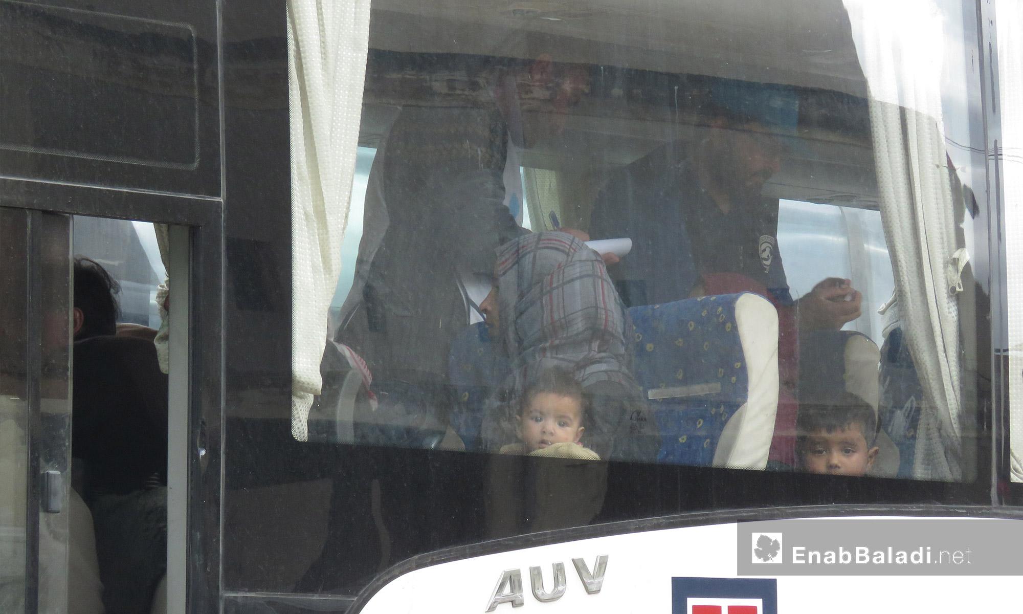 أطفال ومهجرون داخل حافلة وصلت من عربين إلى قلعة المضيق غربي حماة - 25 آذار 2018 (عنب بلدي)