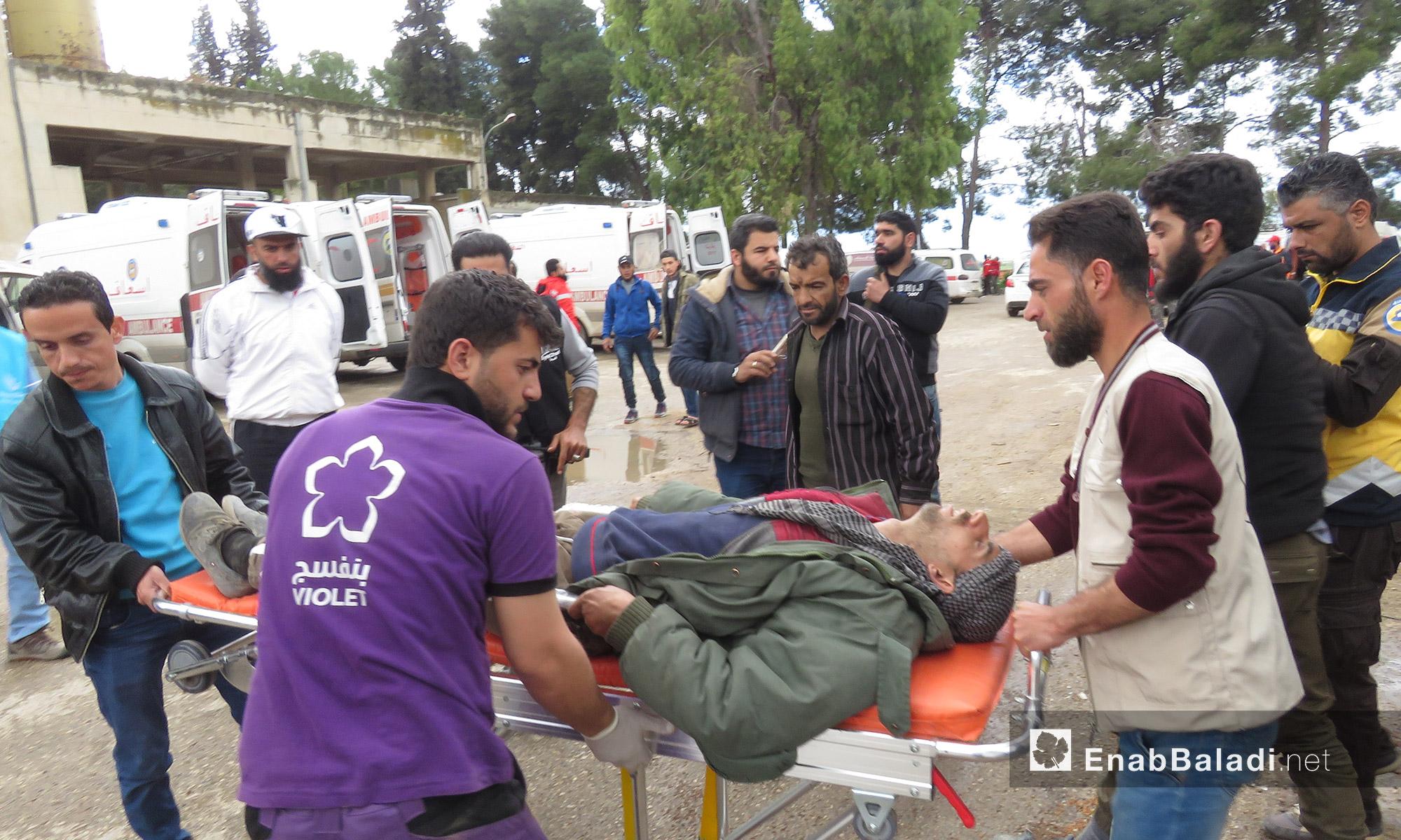 منظمات ومتطوعون ينقلون مصابًا وصل من عربين إلى قلعة المضيق غربي حماة - 25 آذار 2018 (عنب بلدي)