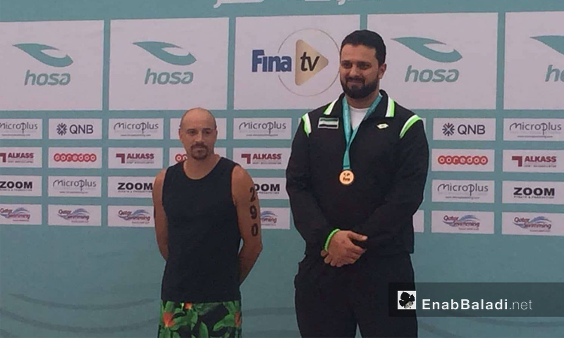 السباح السوري أنس محمود خلال تتويجه في قطر - 16 آذار 2018 (عنب بلدي)