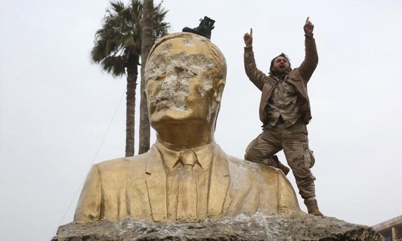 مقاتل من فصائل المعارضة إلى جانب تمثال حافظ الأسد بعد تحطيمه في إدلب - 28 آذار 2015 (ثائر حاج حمدان)