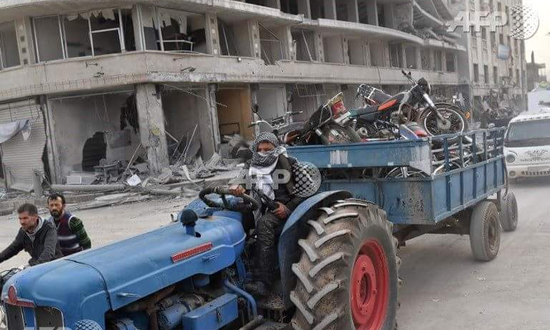 عناصر من الجيش الحر يقدمون على سرقة ممتلكات المدنيين في مدينة عفرين - 18 آذار 2018 (AFP)