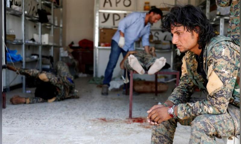 مقاتل من قوات سوريا الديمقراطية يجلس بينما يتلقى رفاقه علاجًا في مستشفى ميداني في الرقة- 28 حزيران 2017 (رويترز)