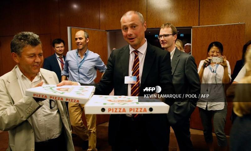 الكولونيل ألكسندر زورين يوزع البيتزا على صحفيين في جنيف - أيلول 2016 (AFP)