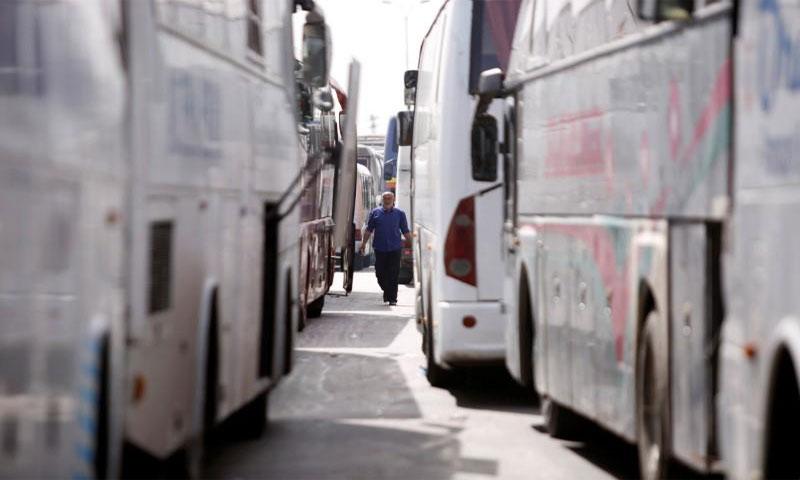سائق يمر وسط حافلات في الغوطة الشرقية بسوريا يوم 3 أبريل نيسان 2018(رويترز)