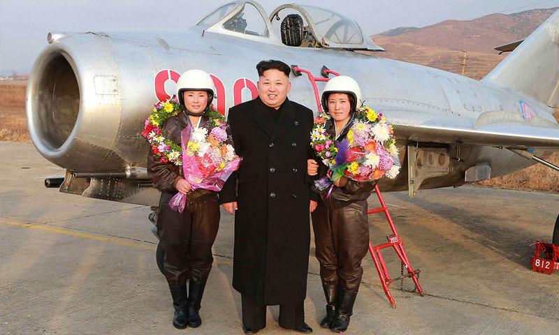 الزعيم الكوري كيم جونغ أون إلى جانب طيارتين تحملان باقات ورد (رويترز)