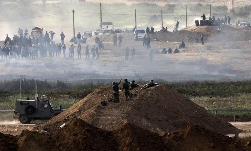 جنود إسرائيليون قرب السياج الأمني بينما محتجون على الجانب الآخر في قطاع غزة 5 نيسان 2018(رويترز)