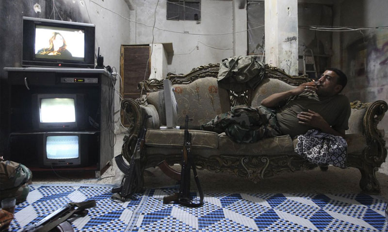 """مقاتل في """"الجيش الحر"""" يشاهد التلفزيون خلال استراحة من المعارك في حلب (رويترز)"""
