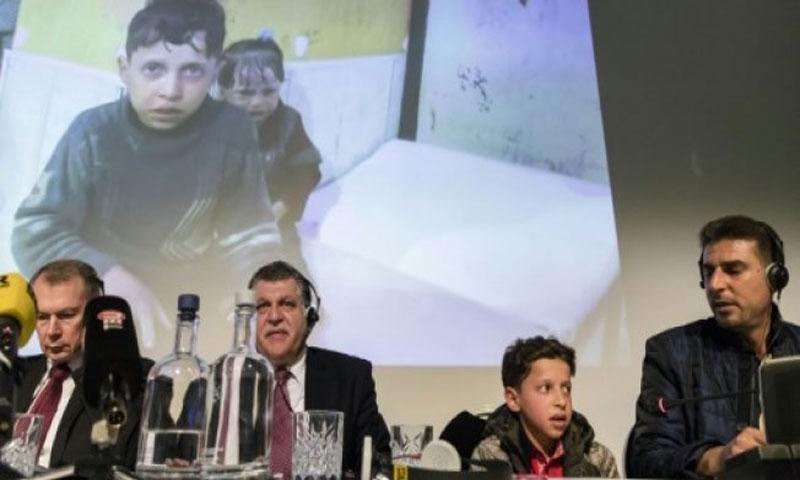 السفير الروسي لدى هولندا الكسندر شولغين (يسار) وإلى جانبه نائب ممثل سوريا لدى منظمة حظر الاسلحة الكيماوية غسان عبيد وصبي ورجل سوريين في مؤتمر صحفي عقد في لاهاي - 26 نيسان 2018 (AFP)