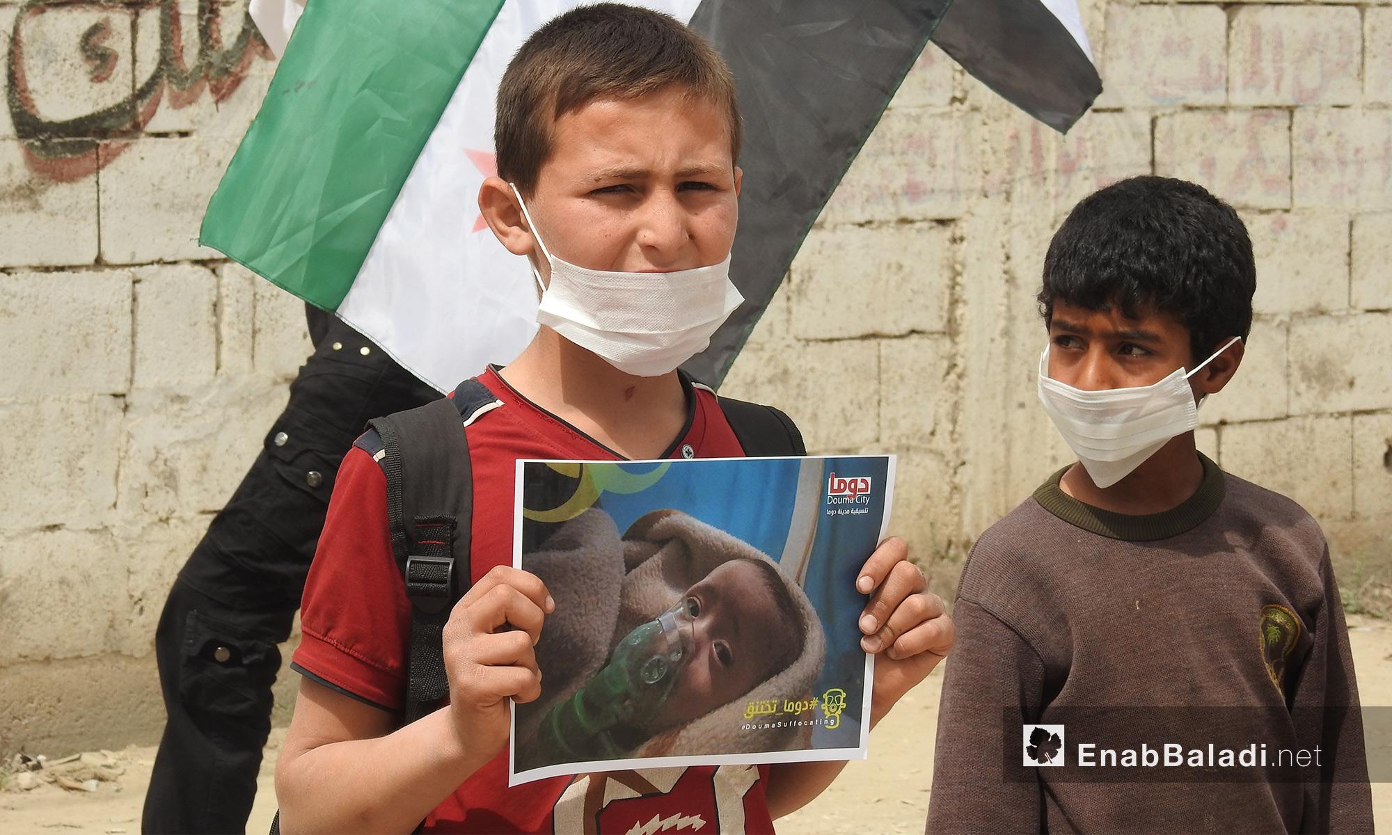 طقل من بلدة دابق شمالي حلب يحمل صورة طفل مختنق بالغازات السامة تضامنًا مع مدينة دوما في الغوطة الشرقية - 8 من نيسان 2018 (عنب بلدي)