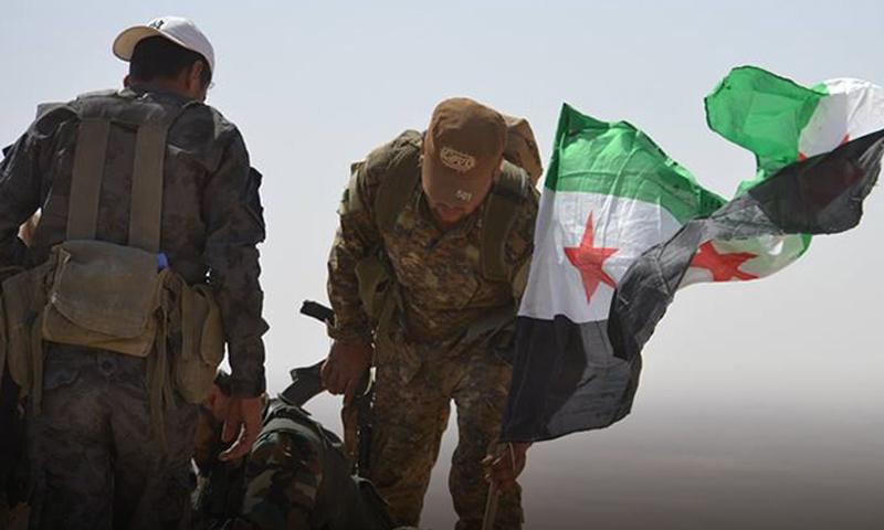عناصر من الجيش الحر يرفعون علم الثورة السورية في القلمون الشرقي - (انترنت)