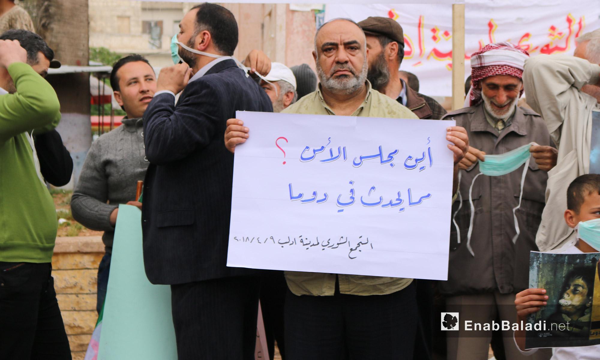 رجل يحمل لافتة خلال وقفة تضامنية لأهالي إدلب مع دوما بعد مجزرة الكيماوي - 9 من نيسان 2018 (عنب بلدي)