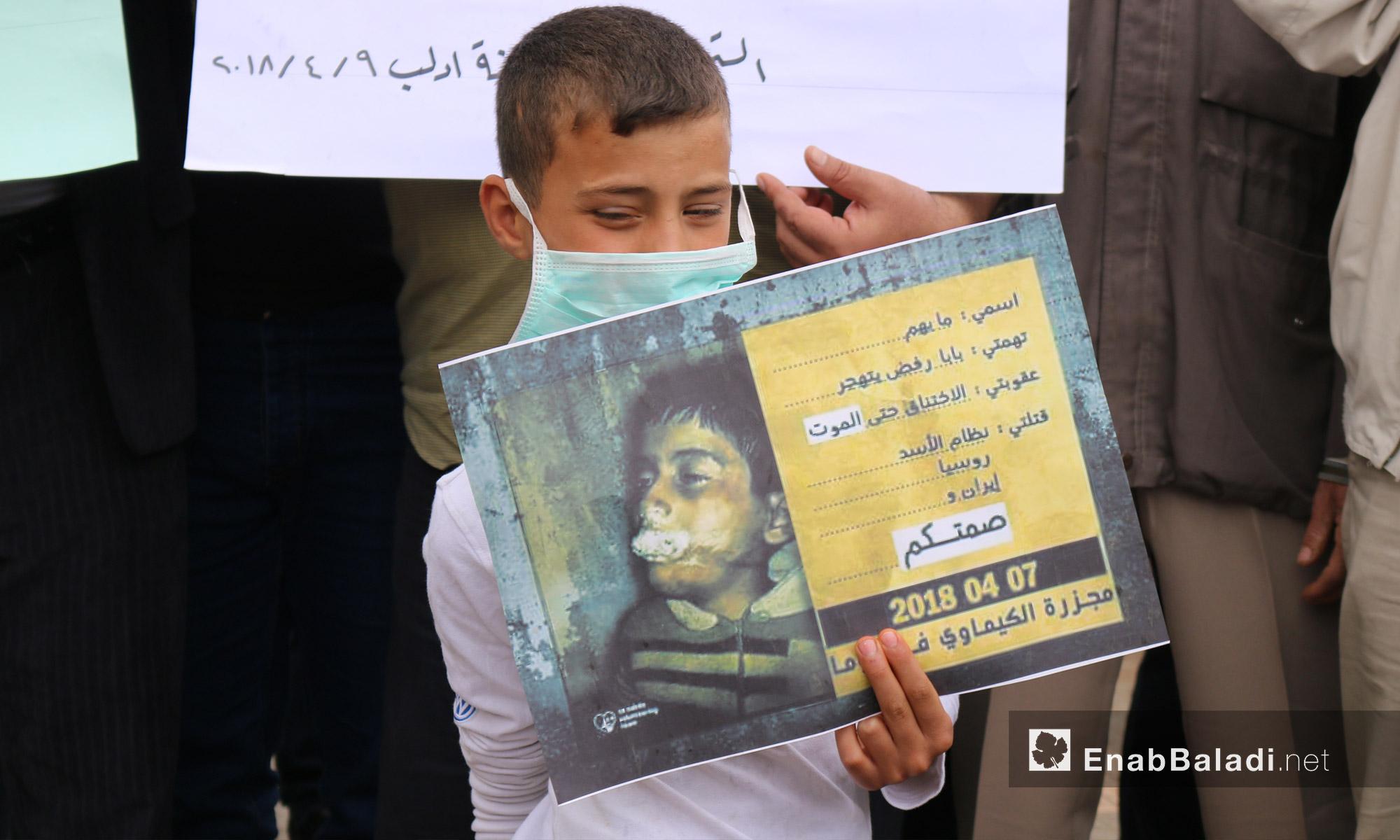 طفل يحمل صورة لأحد ضحايا الغازات السامة خلال وقفة تضامنية لأهالي إدلب مع دوما بعد مجزرة الكيماوي - 9 من نيسان 2018 (عنب بلدي)
