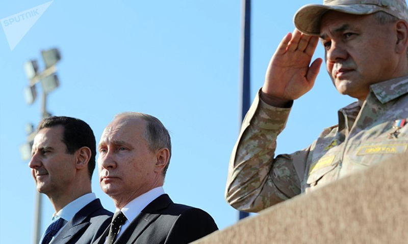 بشار الأسد مع الرئيس الروسي فلاديمير بوتين ووزير دفاعه في قاعدة حميميم - (سبوتنيك)