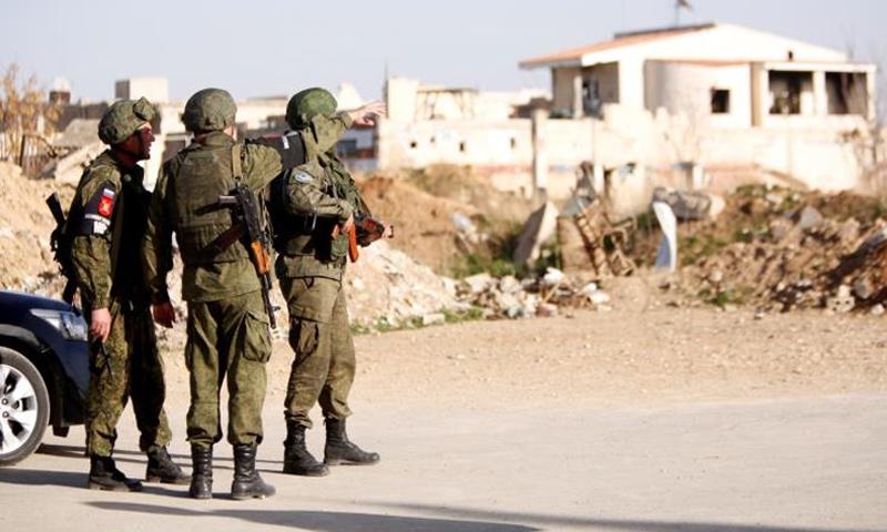 عناصر من الشرطة الروسية على معبر مخيم الوافدين في الغوطة الشرقية - آذار 2018 (رويترز)