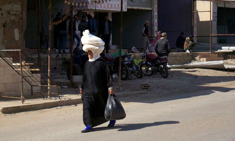 سيدة تحمل ربطات خبز في بلدة الغارية الغربية بريف درعا - 29 شباط 2016 (رويترز)