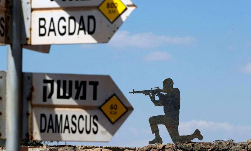 جندي إسرائيلي يقف قرب لافتة لطريقي دمشق وبغداد في هضبة الجولان المحتل - 6 تشرين الأول 2017 (AFP)