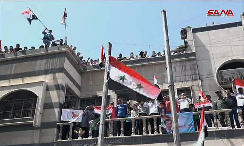 النظام السوري يرفع العلم السوري على مبنى مجلس بلدة يلدا جنوبي دمشق - 11 من أيار 2018 (سانا)