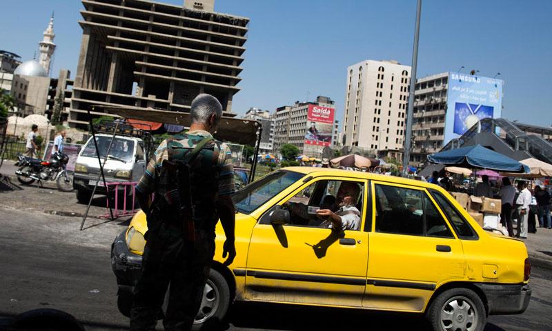 تكسي يقدم أوراقه لحاجز عسكري في شارع الثورة وسط دمشق (andrewmcconnell.com)