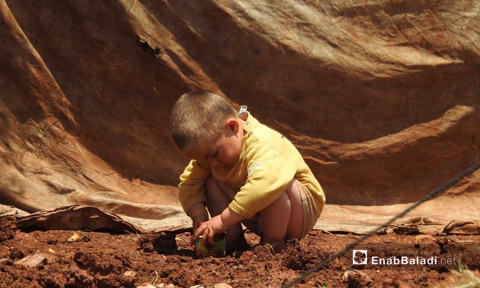 طفل يلعب بالطين قرب خيمة عائلته في ريف حلب الشمالي - 13 من أيار 2018 (عنب بلدي)