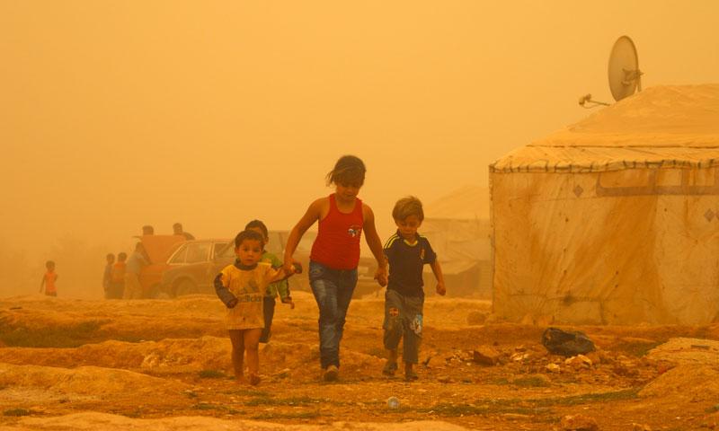 أطفال سوريون يمشون في مخيم بالبقاع اللبناني خلال عاصفة غبارية - 7 أيلول 2015 (AFP)
