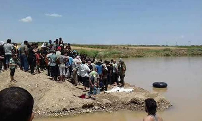 نازحون من جنوبي دمشق ينتشلون جثة المسن أبو عزيز الشهابي بعد غرقه في نهر دير بلوط بريف عفرين - 23 من أيار 2018 (فيس بوك)