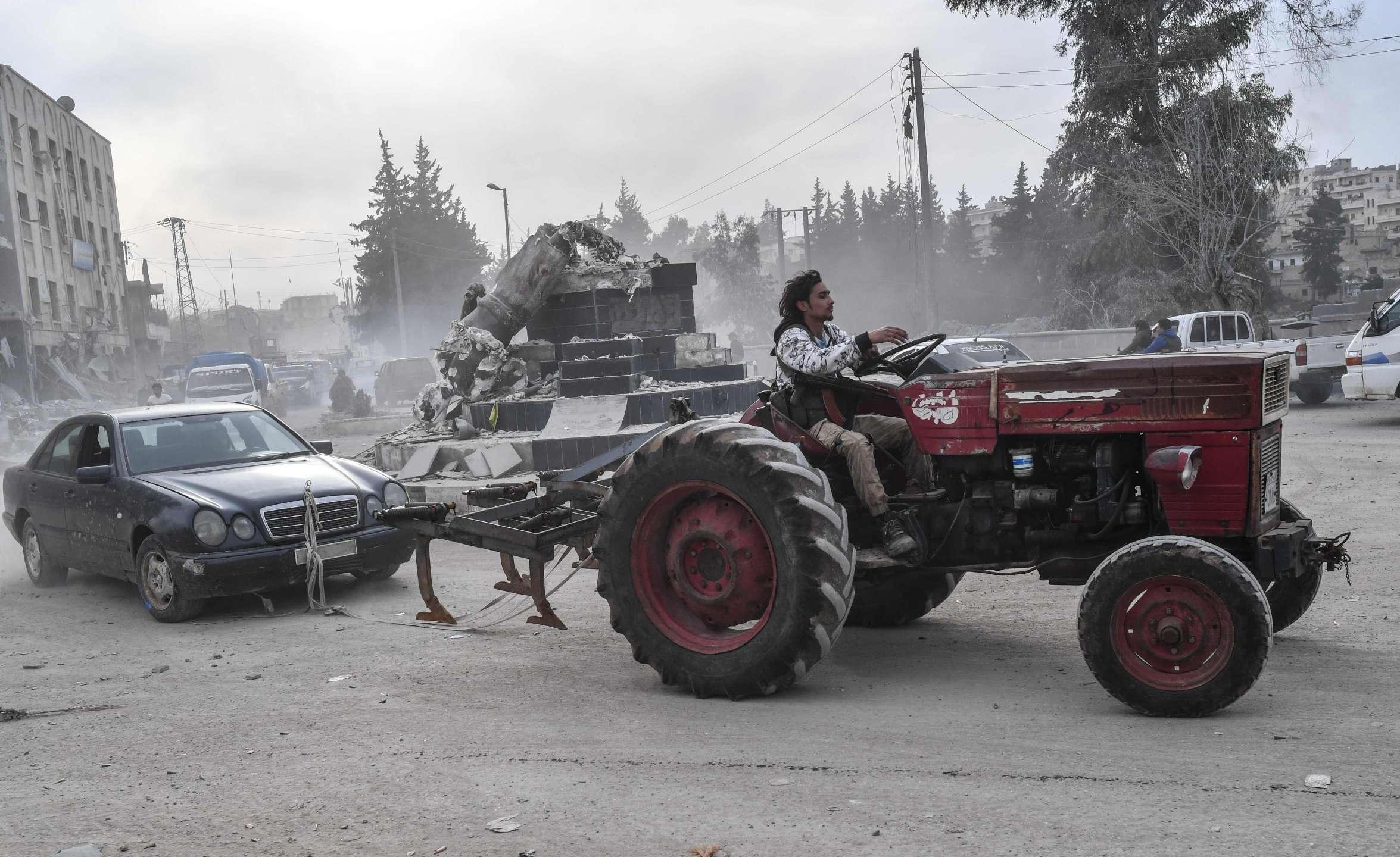 مقاتلون في الجيش الحر يعفشون سيارات وأثاثًا من عفرين (AFP)