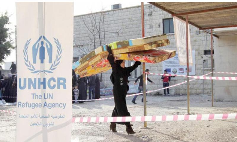 لاجئة سورية تتلقى معونات من مفوضية اللاجئين في لبنان (رويترز)