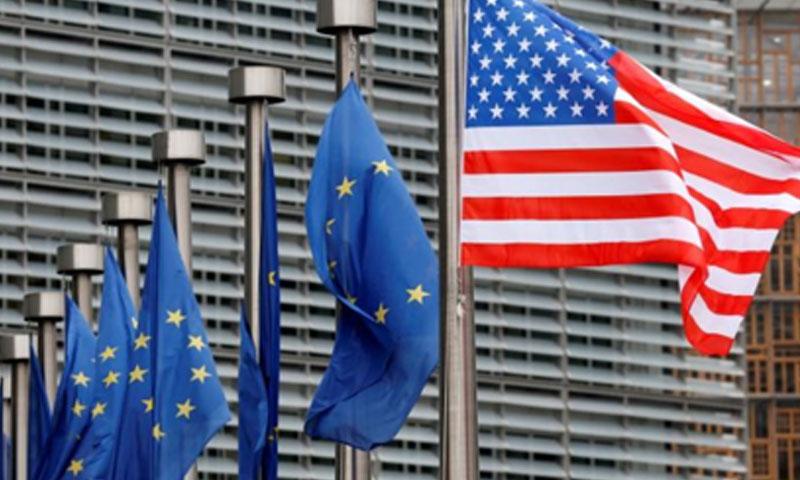 العلم الأمريكي وعلم الاتحاد الأوروبي (رويترز)