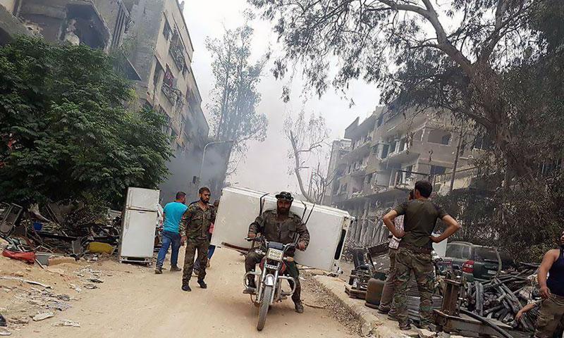 عناصر من قوات الأسد في أثناء قيامهم بحملات تعفيش في مخيم اليرموك 23 من أيار 2018 (فيس بوك)