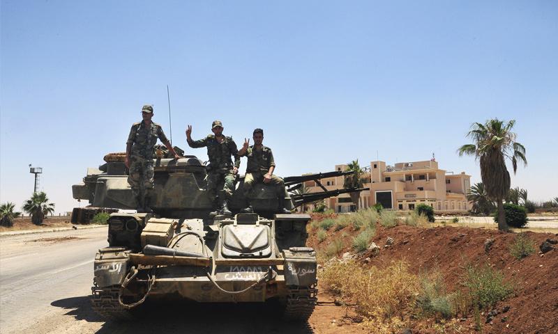عناصر من قوات الأسد يرفعون إشارة النصر بعد السيطرة على معبر نصيب الحدودي - 7 من تموز 2018 (AP)