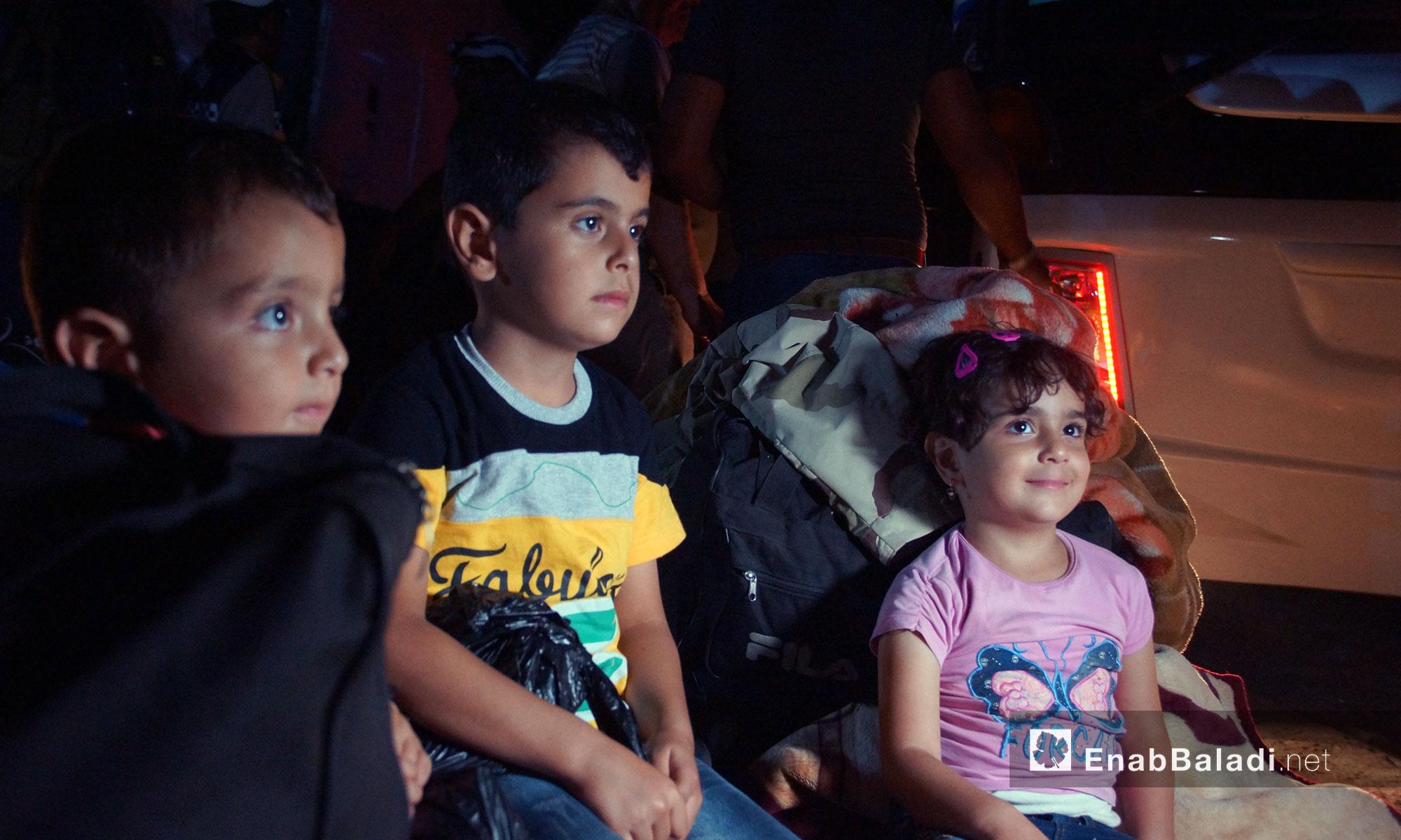 أطفال من مهجري درعا لحظة وصول القافلة الأولى إلى مدينة قلعة المضيق في ريف حماه - 16 تموز 2018 (عنب بلدي)