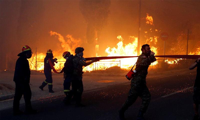رجال الإطفاء يحاولون إخماد حريق قرب العاصمة اليونانية أثينا (رويترز)
